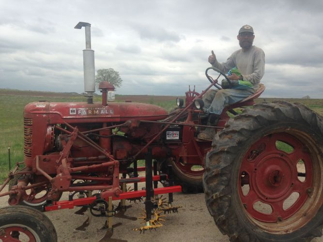 Farmer Adam on his Cultivating Tractor